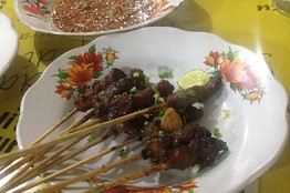 A portion of sate matang consists of lamb or beef satay, peanut sauce, meat broth, and rice. Resty Woro Yuniar/The Wall Street Journal