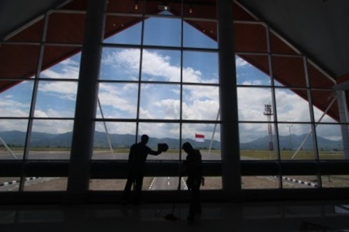 "Airport officials clean the windows at the departure terminal of Rembele Airport in Bener Meriah regency in Aceh on Tuesday. President Joko ""Jokowi"" Widodo inaugurated the newly renovated airport on Wednesday. The government hopes for tourist arrivals in Aceh to increase thanks to the airport expansion.(Antara/Septianda Perdana)"